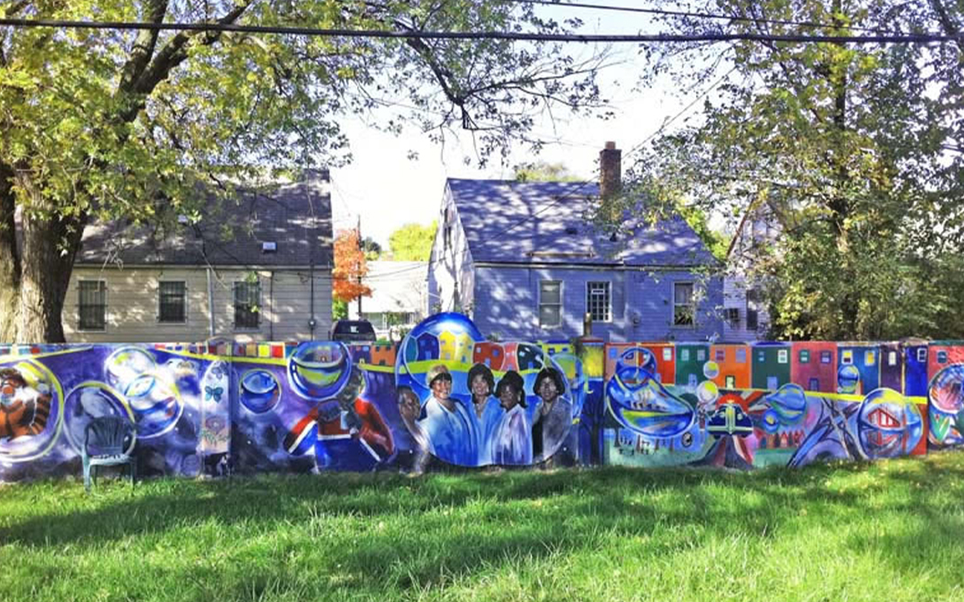 Among the houses in this residential neighborhood, a wall wall erected to segregate by race has been reclaimed and turned into a large community art project.