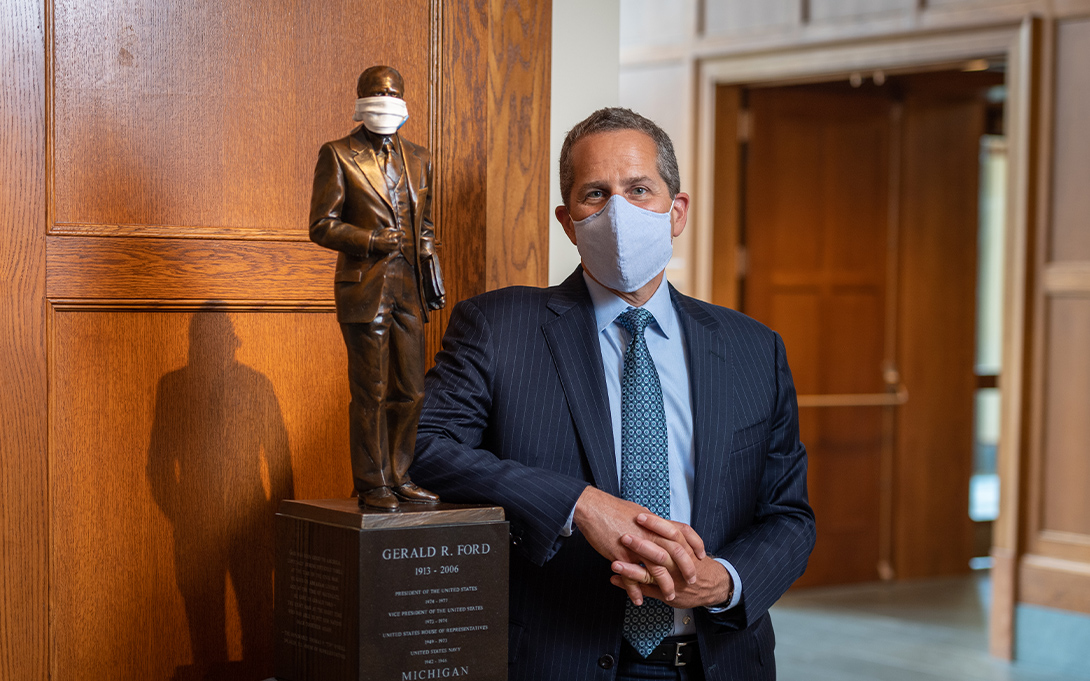 Michael Barr and a scaled replica statue of Gerald R. Ford, both masked amid the COVID-19 pandemic