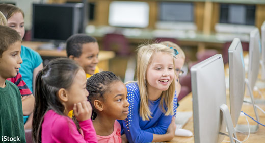 Photo of children looking at computer
