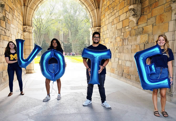 "Photo of students holding letter-shaped balloons that spell out ""Vote"""
