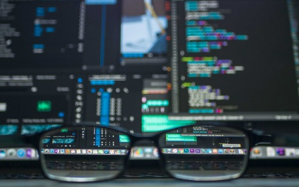 Glasses rest on a desktop with various coding windows open on a screen behind