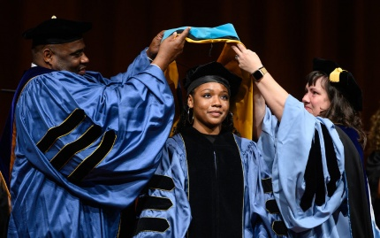 PhD student getting hooded at commencement