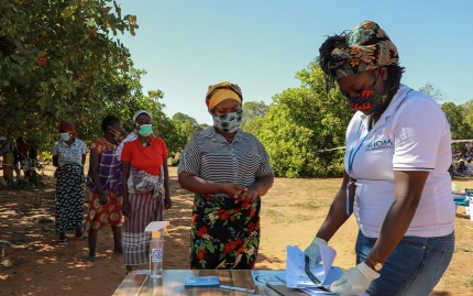 Photo of women in Mozambique, masked and socially distanced, waiting in a queue