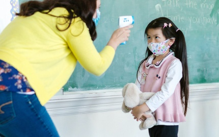 A teacher takes the temperature of a masked young student next to the class blackboard