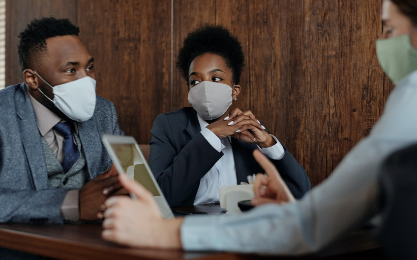 Three people, wearing masks, at a meeting.