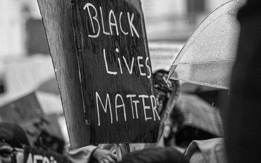 "A rainy protest with a sign reading ""Black Lives Matter"""