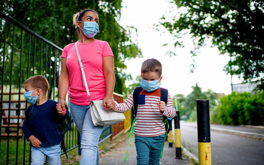 A parent/guardian and two young children in masks walking outdoors (Credit: Shutterstock)