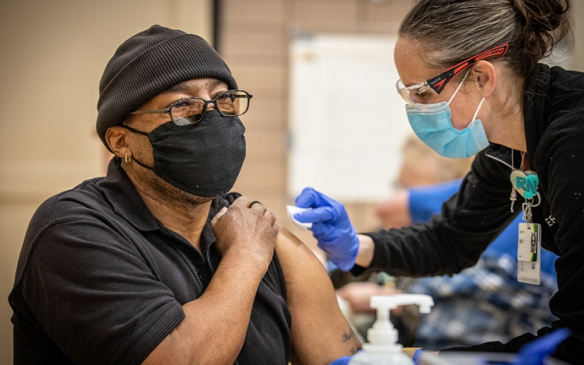 A nurse administers the COVID-19 vaccine to a teacher in Iowa (Credit: Phil Roeder / CC BY)