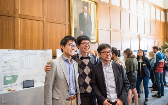 Three Ford School graduate students in the Great Hall, beneath a portrait of President Ford