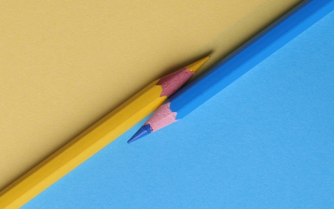 Yellow and blue pencils diagonally bisect a colored background