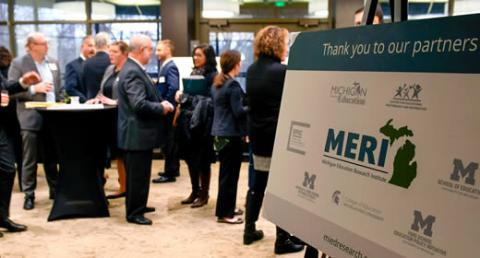 Photo of a posterboard of MERI partners in the foreground; with kickoff event attendees networking in the background